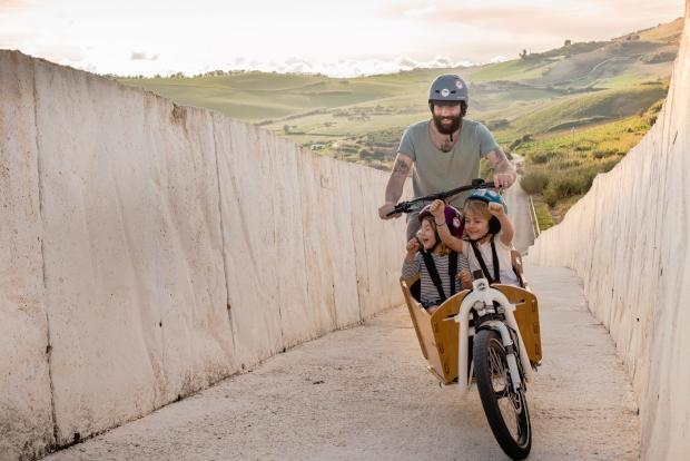 Cycliste transportant ses deux enfants dans un vélo cargo
