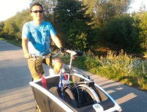 Homme qui transporte un vélo pliant dans un cargobike